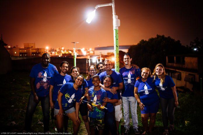 Voluntários Litro de Luz comemoram a chegada de mais um poste em comunidade carente. Foto - Litros de Luz - Divulgação