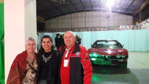 A jovem Bárbara com dois amigos que, como ela, são apaixonados pelo Alfa Romeo (fundo)