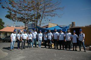 Grupo de voluntários pouco antes de iniciar os trabalho de reforma de mais uma casa.