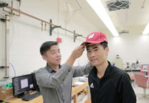 Professor Xudong Wang, especialista em engenharia de materiais da UW-Madison, testa boné em usuário. Foto: UWM