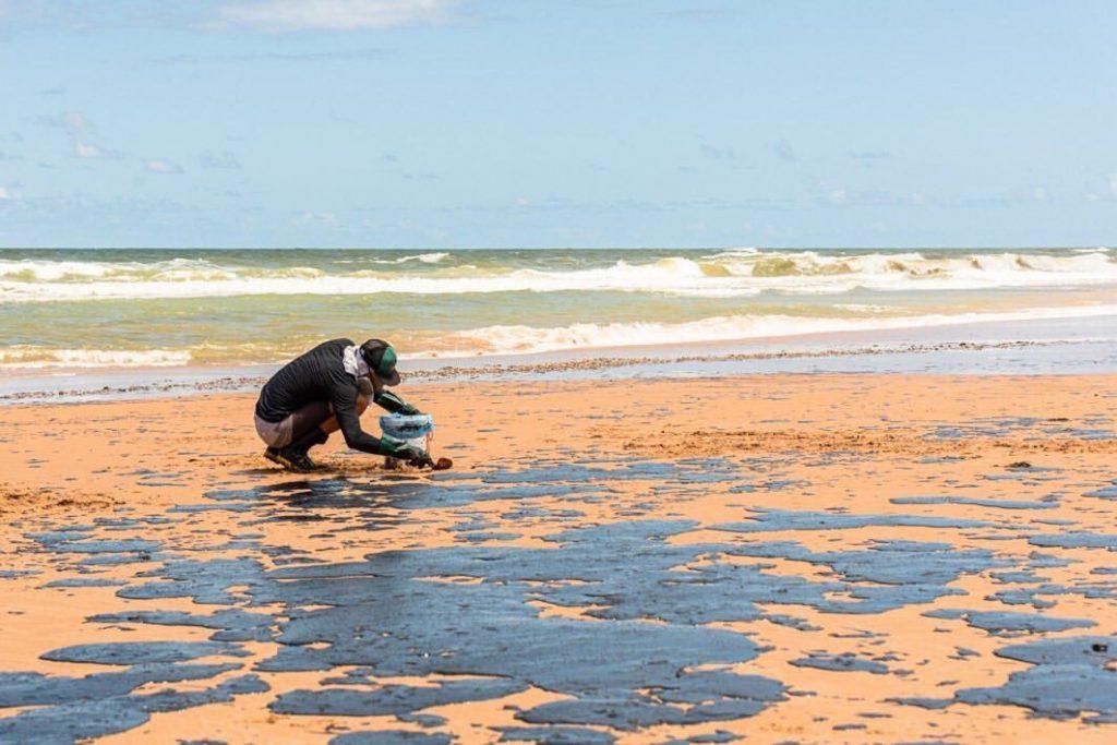 Voluntário limpa óleo de uma praia da Bahia. Todos os estados do Nordeste foram atingidos, com grandes danos ao meio ambiente. Foto - Matheus Morback